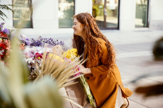 Zijaanzicht van smileyvrouw die lentebloemen buitenshuis krijgen