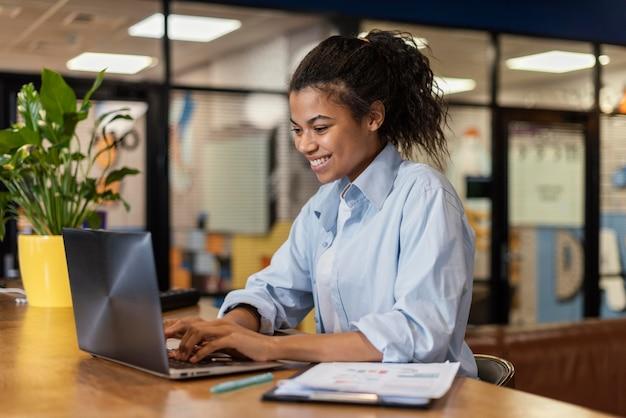 Zijaanzicht van smileyvrouw die met laptop op kantoor werkt