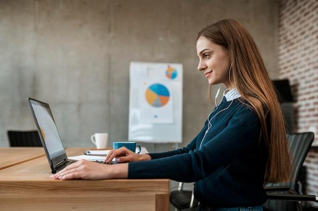 Zijaanzicht van smileyvrouw die met laptop voor een vergadering voorbereidingen treffen