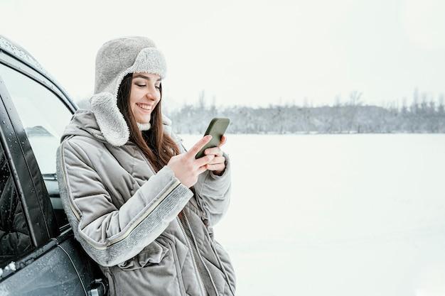 Zijaanzicht van smileyvrouw die smartphone gebruikt terwijl op een roadtrip met exemplaarruimte