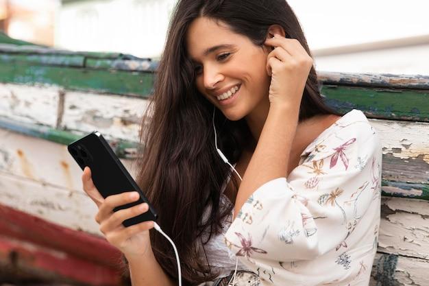 Zijaanzicht van smileyvrouw die smartphone met oortelefoons buitenshuis gebruikt