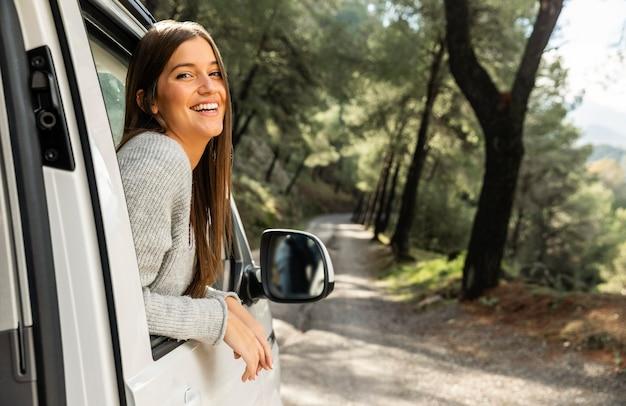 Zijaanzicht van smileyvrouw in de auto tijdens een roadtrip