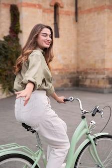 Zijaanzicht van smileyvrouw in de stad die een fiets berijdt