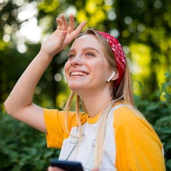 Zijaanzicht van smileyvrouw in openlucht met smartphone