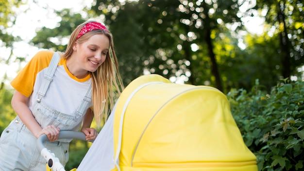 Zijaanzicht van smileyvrouw in openlucht met wandelwagen