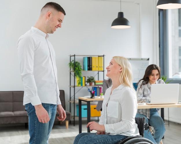 Zijaanzicht van smileyvrouw in rolstoel die met medewerker converseren