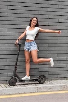 Zijaanzicht van smileyvrouw poseren met scooter buiten