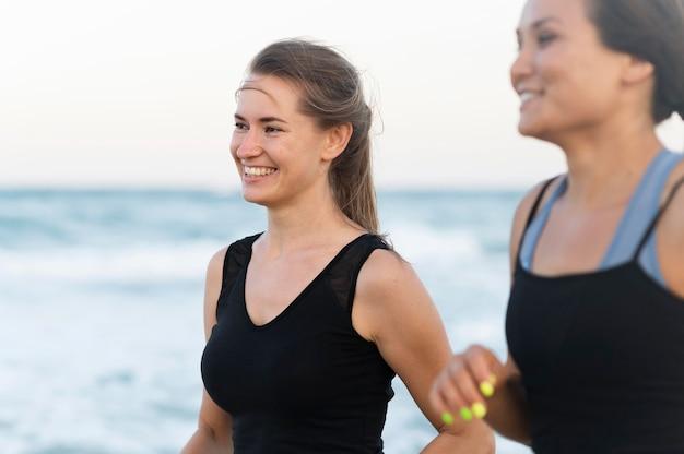 Zijaanzicht van smileyvrouwen die op het strand uitoefenen