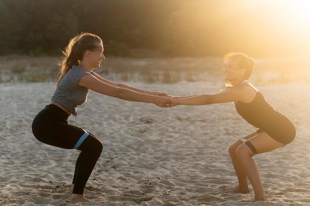 Zijaanzicht van smileyvrouwen die samen op het strand uitwerken