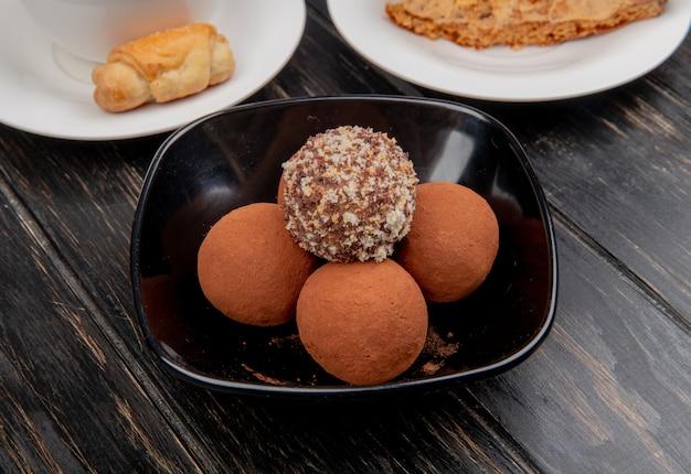 Zijaanzicht van snoep in kom met bakkerijproduct op schotel op houten oppervlakte