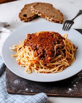 Zijaanzicht van spaghetti bolognese op witte plaat