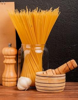 Zijaanzicht van spaghettideegwaren in kruik met zoute zwarte peper in knoflookmaalmachine en knoflook met blocnote op houten oppervlakte