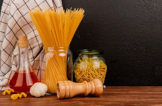 Zijaanzicht van spaghettideegwaren in kruiken met gesmolten boterzout van het knoflook en geruite doek op houten oppervlakte en zwarte achtergrond met exemplaarruimte