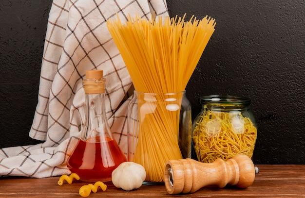 Zijaanzicht van spaghettideegwaren in kruiken met gesmolten boterzout van het knoflook en geruite doek op houten oppervlakte