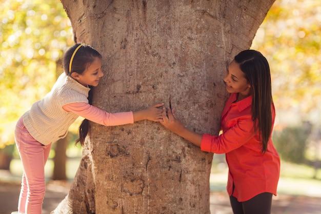 Zijaanzicht van speelse moeder met dochter in het park