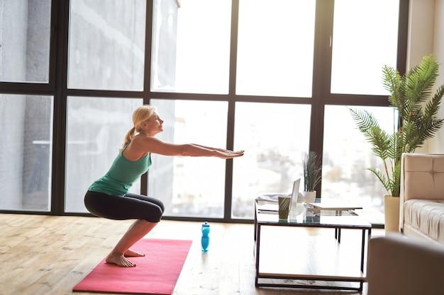 Zijaanzicht van sportieve volwassen vrouw die thuis yoga beoefent na online videoles op een laptop