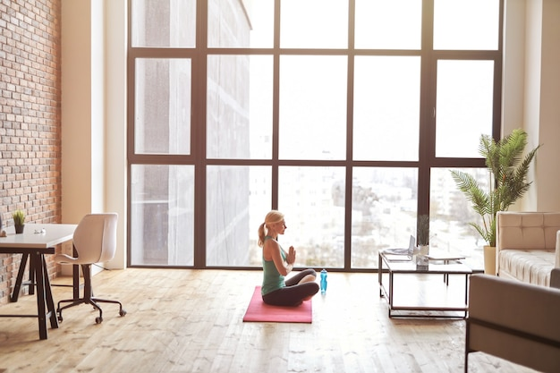 Zijaanzicht van sportieve volwassen vrouw zittend op een mat en kijken naar online video-tutorial met behulp van laptop