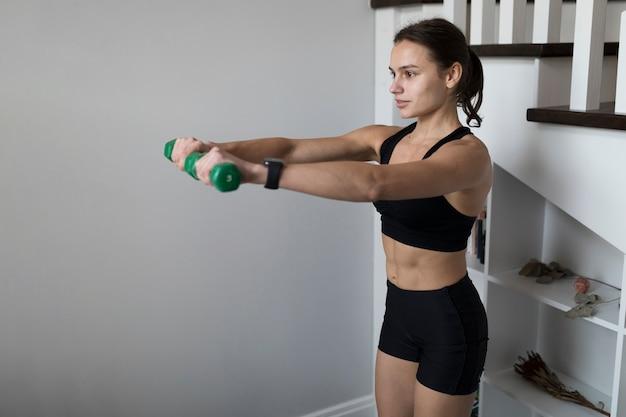 Zijaanzicht van sportieve vrouw die gewichten met exemplaarruimte gebruikt