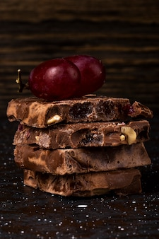 Zijaanzicht van stapel melk en donkere chocolade met notenvruchten en bessen en pijpjes kaneel op donkere achtergrond
