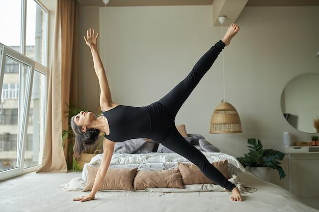 Zijaanzicht van sterke atletische jonge vrouw die yoga beoefent in gezellige slaapkamer, staande in siide plank oefening