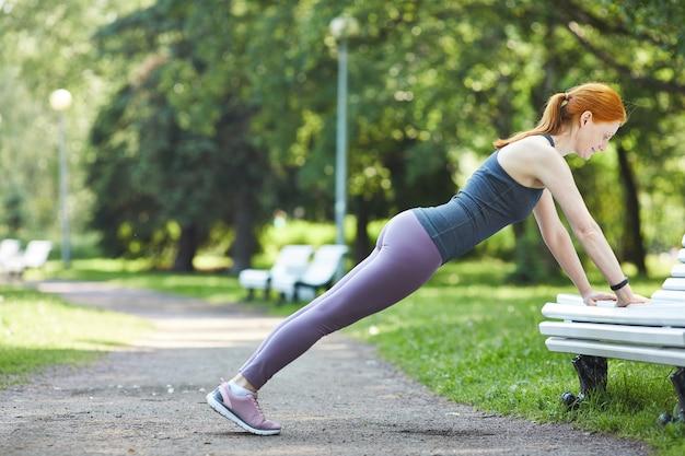 Zijaanzicht van sterke rijpe roodharige vrouw in beenkappen die push-ups doen vanaf bankje in stadspark