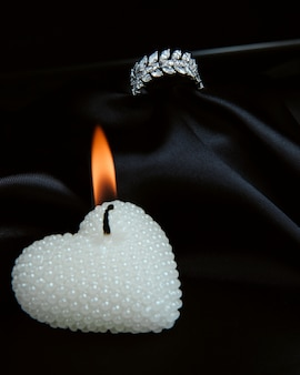 Zijaanzicht van sterling zilveren ring met diamanten en met brandende decoratieve kaars in een hartvorm op zwarte muur