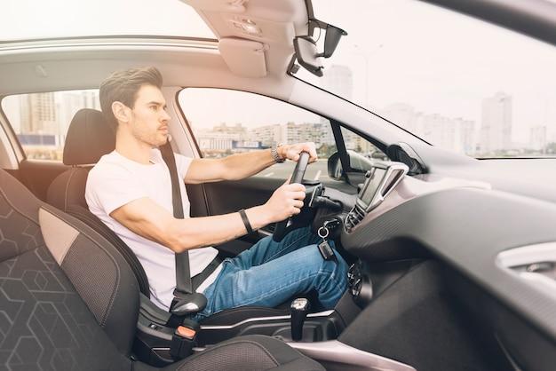 Zijaanzicht van stijlvolle jongeman rijden luxe auto