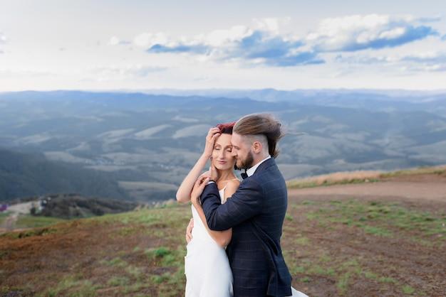 Zijaanzicht van stijlvolle man knuffelt een roodharig meisje in een veld en de wind ontwikkelt hun haar