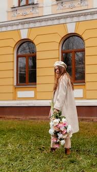 Zijaanzicht van stijlvolle vrouw met boeket bloemen buiten in de lente