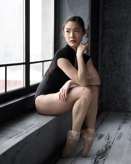 Zijaanzicht van stoïcijnse ballerina poseren bij het raam
