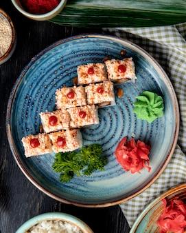 Zijaanzicht van sushi rolt met rijst garnalen tempura avocado en kaas binnen op een bord met gember en wasabi
