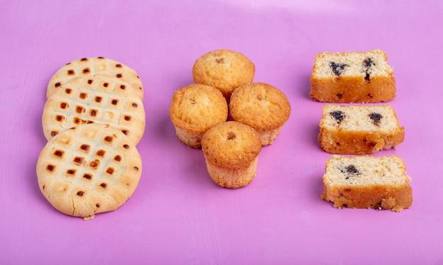 Zijaanzicht van taarten en muffins en koekjes op paars