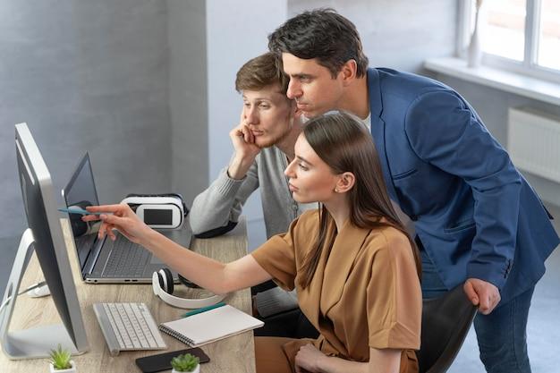Zijaanzicht van team van professionals die werken met nieuwe technologie