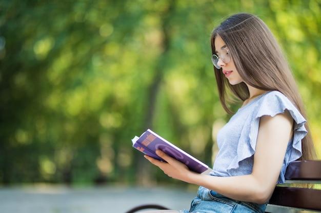 Zijaanzicht van tevreden brunette vrouw in bril zittend op een bankje en leesboek in park