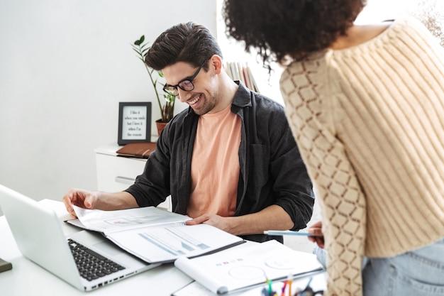 Zijaanzicht van tevreden jonge collega's die laptopcomputer gebruiken bij de tafel terwijl ze op kantoor zijn