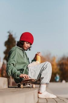 Zijaanzicht van tiener die lunch in het park op skateboard heeft