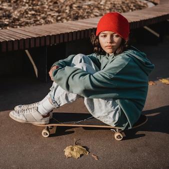 Zijaanzicht van tiener met skateboard buitenshuis