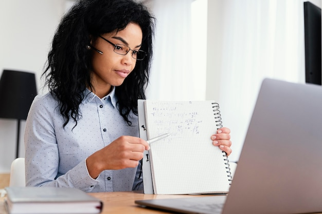 Zijaanzicht van tienermeisje thuis tijdens online school met laptop en notebook