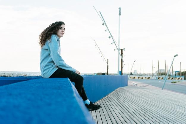 Zijaanzicht van tienerzitting op een blauwe muur die camera kijken