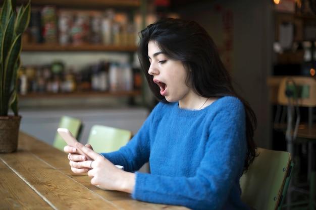 Zijaanzicht van toevallige meisje het letten op smartphone en het kijken verbaasd met nieuws terwijl het zitten in cafetaria