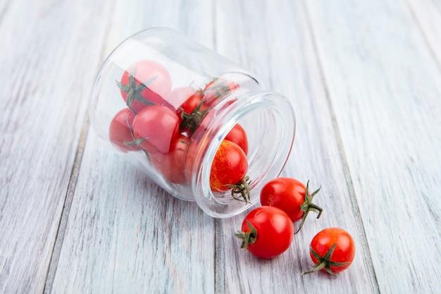 Zijaanzicht van tomaten die uit kruik op hout morsen