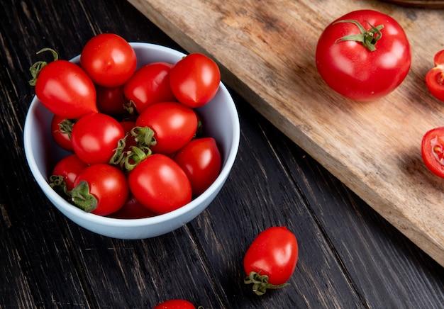 Zijaanzicht van tomaten in kom en andere op snijplank op houten tafel