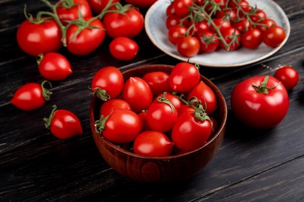 Zijaanzicht van tomaten in kom en plaat en andere op houten tafel