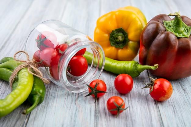 Zijaanzicht van tomaten morsen uit pot met paprika op hout
