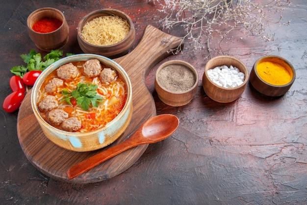 Zijaanzicht van tomatengehaktballetjessoep met noedels in een bruine kom en verschillende kruidenoliefles-ui-knoflook op donkere achtergrondafbeelding