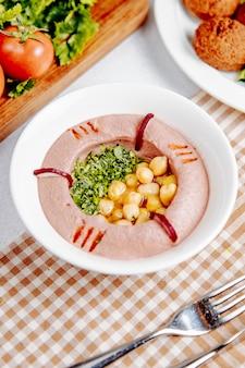 Zijaanzicht van traditionele hummus uit het midden-oosten met kikkererwten en olijfolie