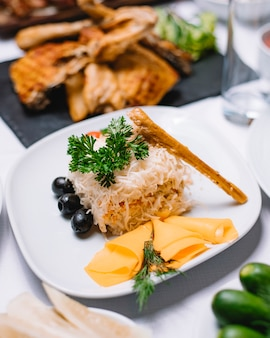 Zijaanzicht van traditionele russische salade mimosa met cannad vis aardappelen kaas wortelen en eieren versierd met zwarte olijven en verse kruiden op een witte plaat