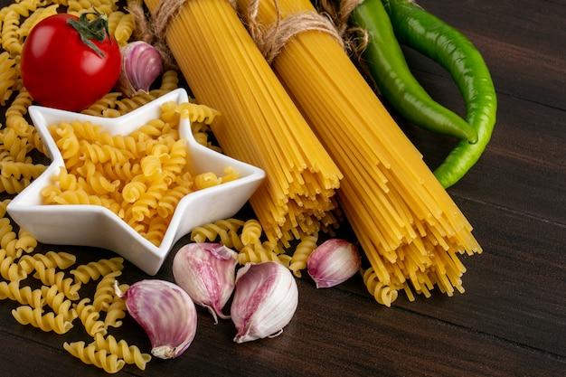 Zijaanzicht van trossen rauwe pasta met knoflook en pasta met tomaat en hete peper op een houten oppervlak