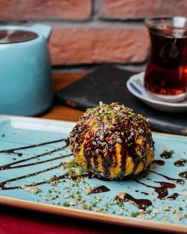 Zijaanzicht van turks dessert gebakken ijs bedekt met chocolade siroop op tafel
