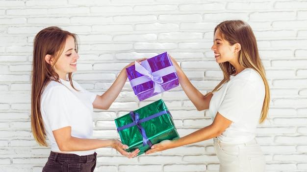 Zijaanzicht van twee gelukkige vrouwelijke vrienden die gift geven aan elkaar